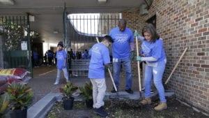 Comcast Cares Day volunteers rake a garden bed.