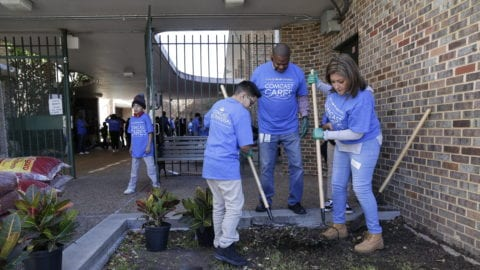 Comcast Cares Day volunteers rake a garden bed.