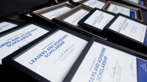 Rows of framed Leaders and Achievers Scholarship certificates.