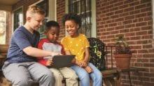Three children sit together on a porch.