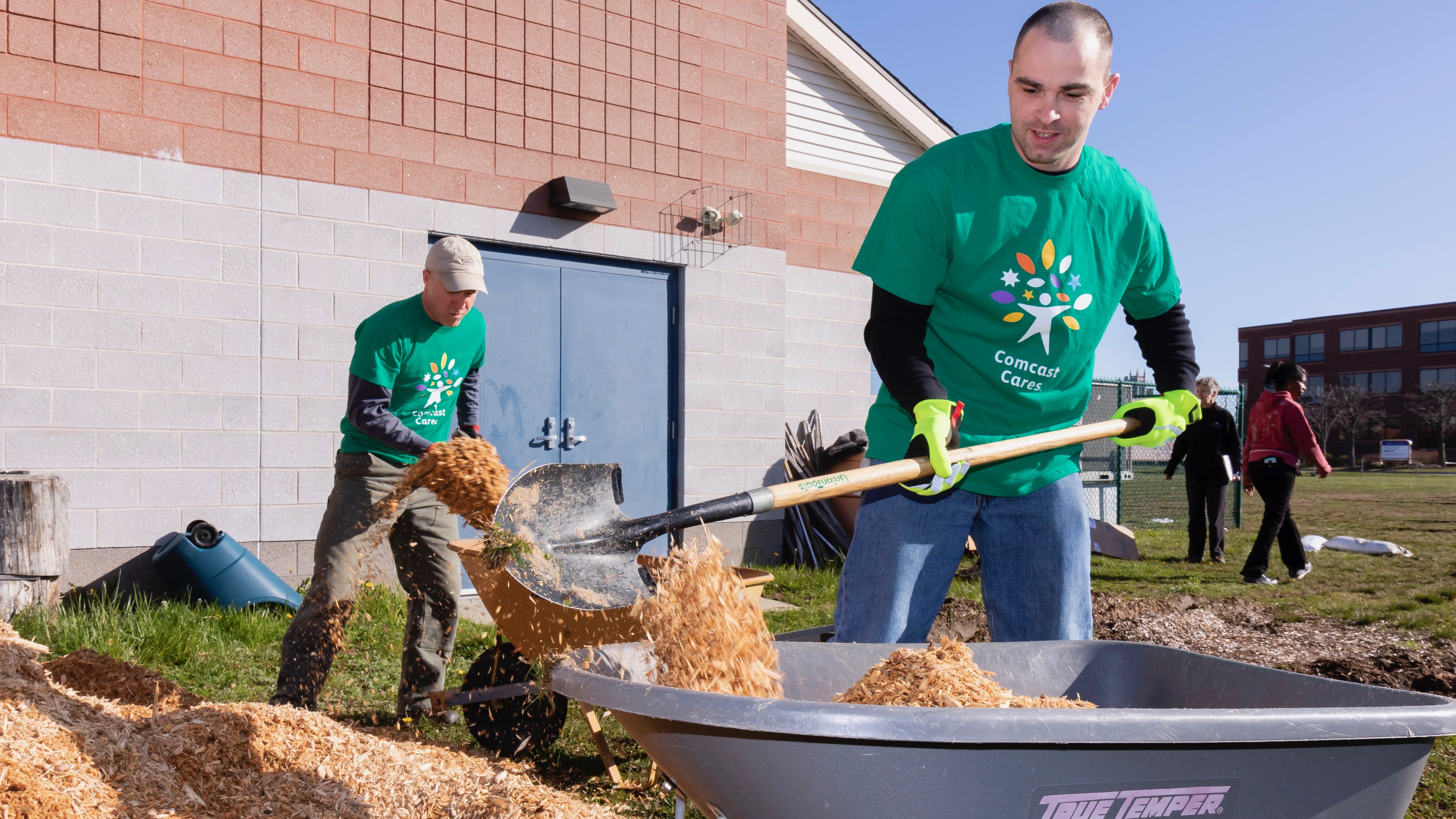 A Comcast Cares Day volunteer fills a wheelbarrow with mulch.