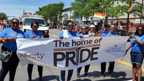 Pride parade with a banner being held by a few people