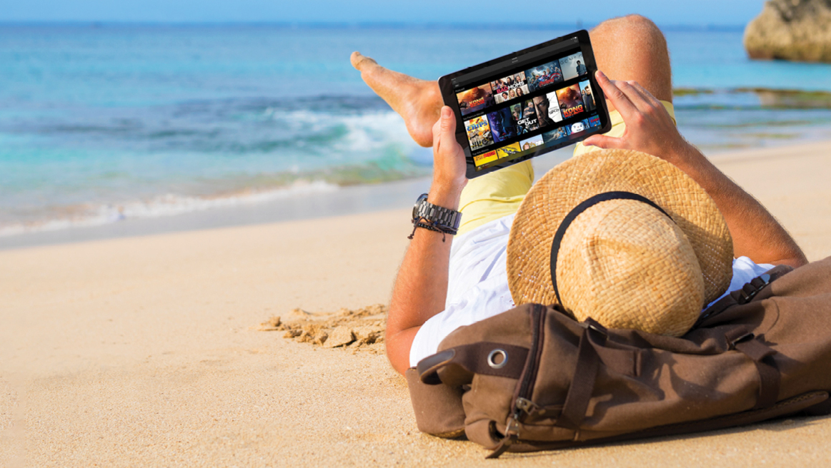 A person uses a tablet as they lie on a beach.