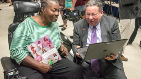 David L. Cohen presents an Internet Essentials participant with a laptop.