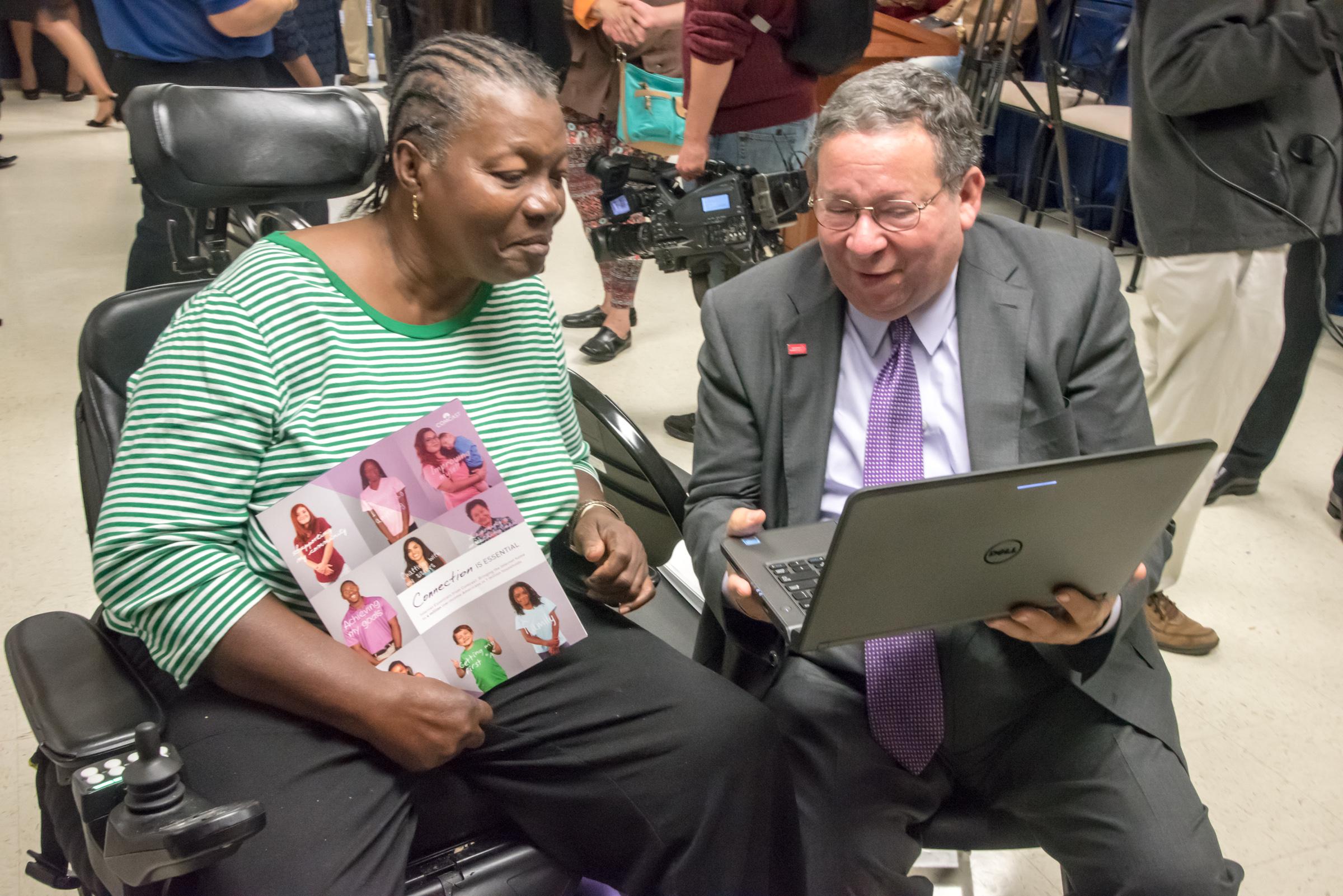 David L. Cohen presents an Internet Essentials participant with a laptop.