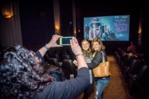 person taking photo of two people standing in front of movie screen