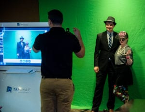 people dressed in 1950s outfits getting photo taken in front of green screen