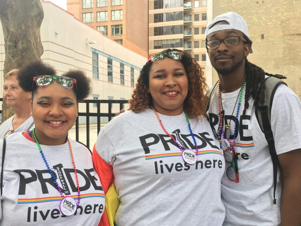 "Three Comcast employees wearing shirts that say ""Pride lives here."""