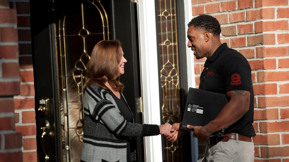 Comcst technician shaking a customer's hand at their front door