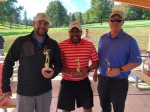 three men holding trophies at a golf course