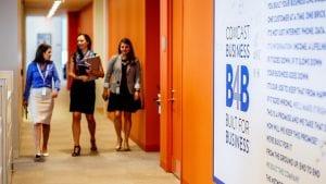 Women walking down a hallway past a Comcast Business logo