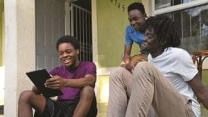 Three teen boys sitting on steps, looking at a tablet