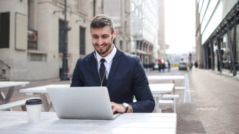 Man typing on a laptop outside