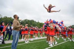 Cheerleader jumping as Craig Melvin watches
