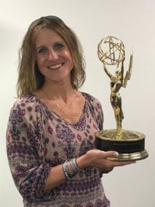 Comcast employee holding an Emmy Award