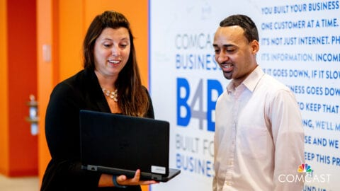 Woman with laptop speaking to man with Comcast Business logo in background