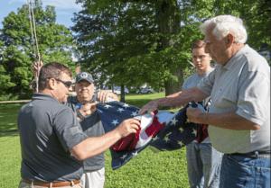 Comcast employees folding American flag