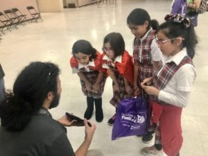 Comcast technician, Axel Hernandez, showing students his technology during the Discovery Festival.