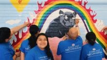 Comcast Cares Day volunteers paint a mural.