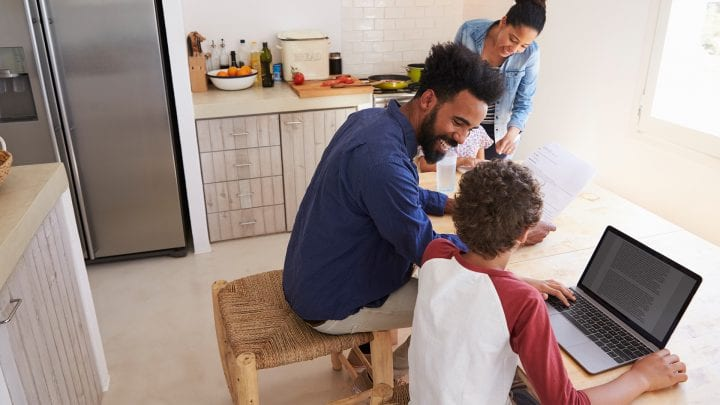 A woman, man and two children sitting at a table looking at a computer.